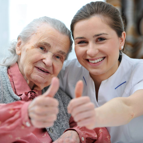 senior woman and female caregiver are showing thumbs up