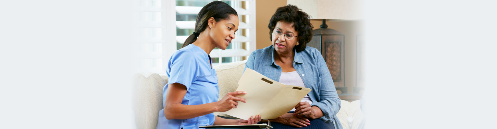 Nurse Discussing Records With Senior Female Patient During Home Visit Talking