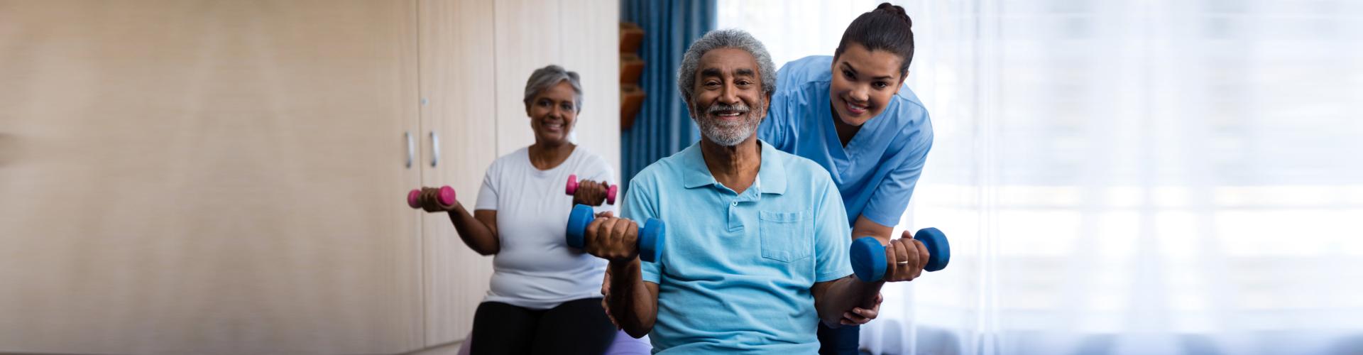 Portrait of nurse training seniors in lifting dumbbells at nursing home