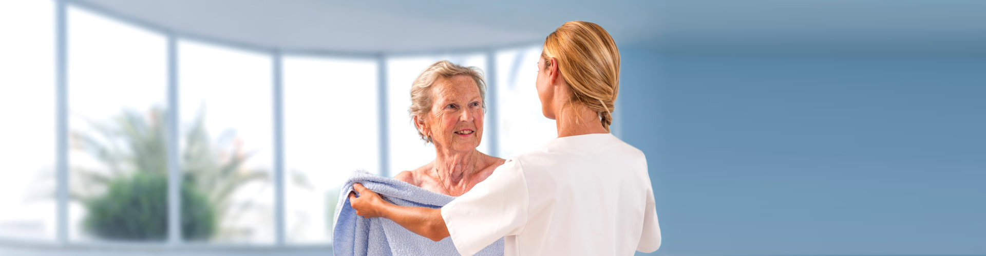 female caregiver giving towel to her old woman patient
